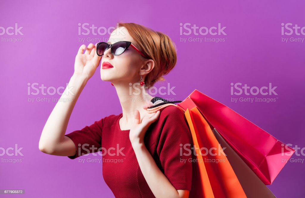 photo of beautiful young woman with colorful shopping bags on the wonderful purple background stock photo