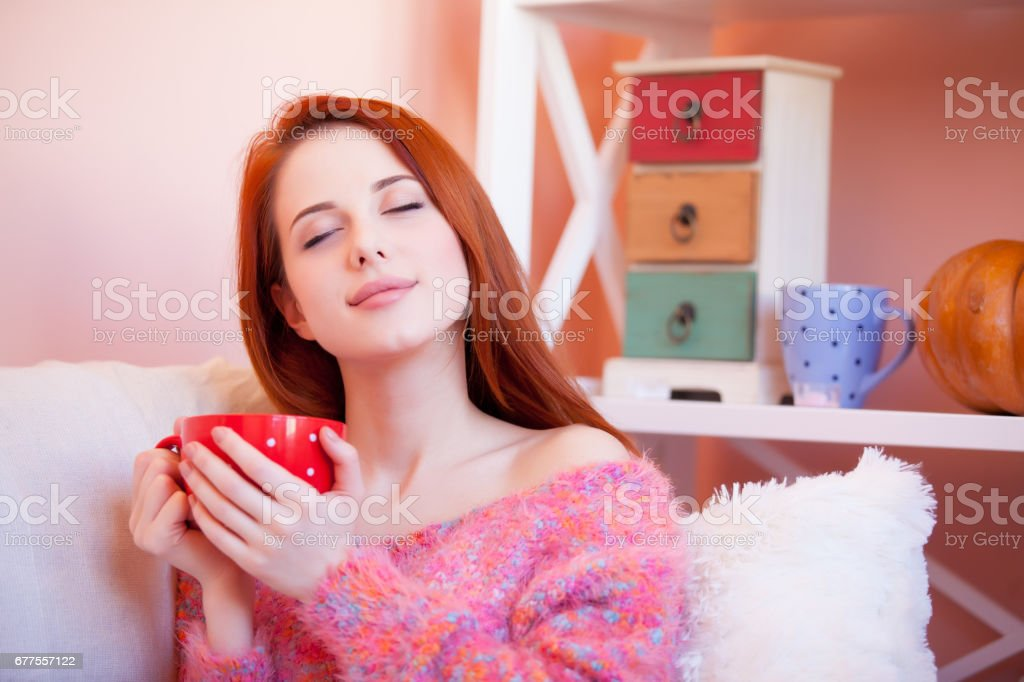photo of beautiful young woman with cup of coffee relaxing on the sofa royalty-free stock photo