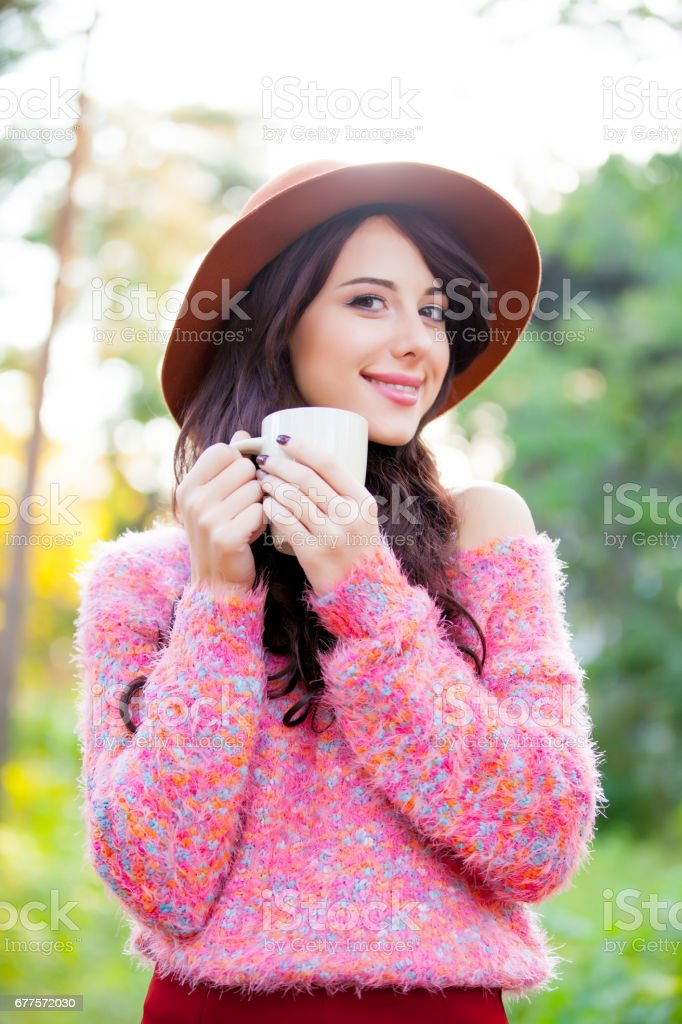 photo of beautiful young woman with cup of coffee standing in the park royalty-free stock photo