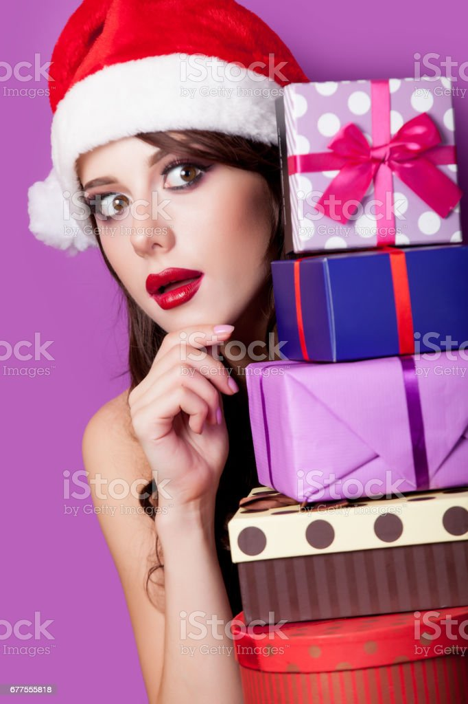 photo of beautiful young woman with gifts in santa claus hat on the wonderful purple background royalty-free stock photo