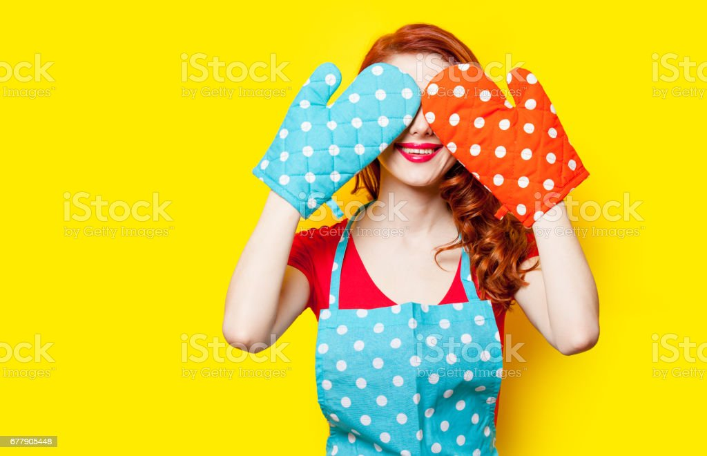 photo of beautiful young woman with potholders on the wonderful yellow studio background royalty-free stock photo