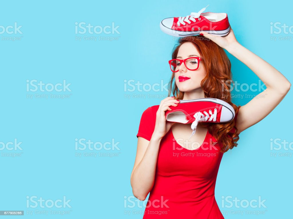 photo of beautiful young woman with red gumshoes on the wonderful blue background royalty-free stock photo