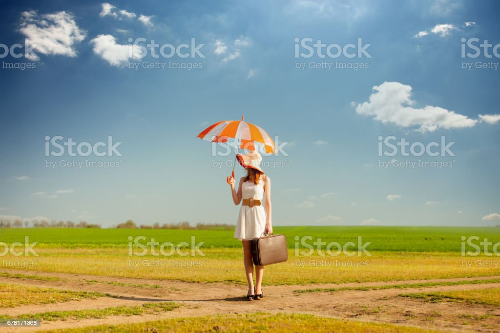 photo of beautiful young woman with suitcase and umbrella on the road near field background stock photo