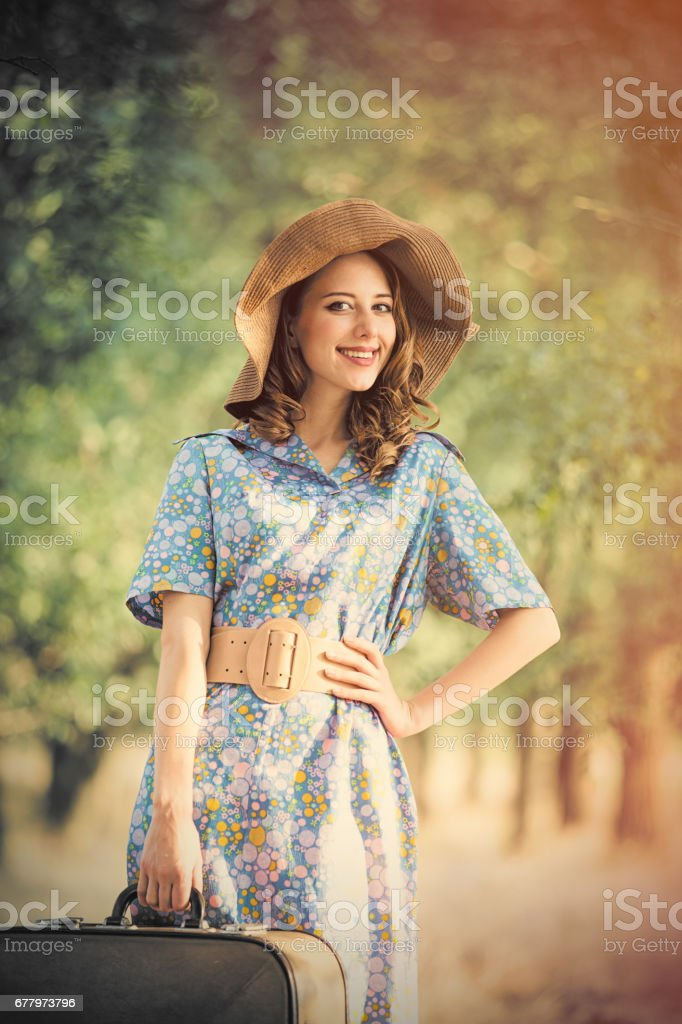 photo of beautiful young woman with suitcase on the wonderful trees background royalty-free stock photo