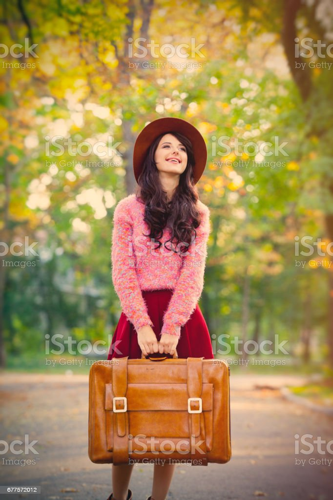 photo of beautiful young woman with suitcase standing in the park royalty-free stock photo