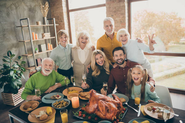 photo of big family standing hugging feast table holiday roasted turkey making portrait relatives multi-generation raising wine glasses show v-sign in living room indoors - family gatherings stock pictures, royalty-free photos & images