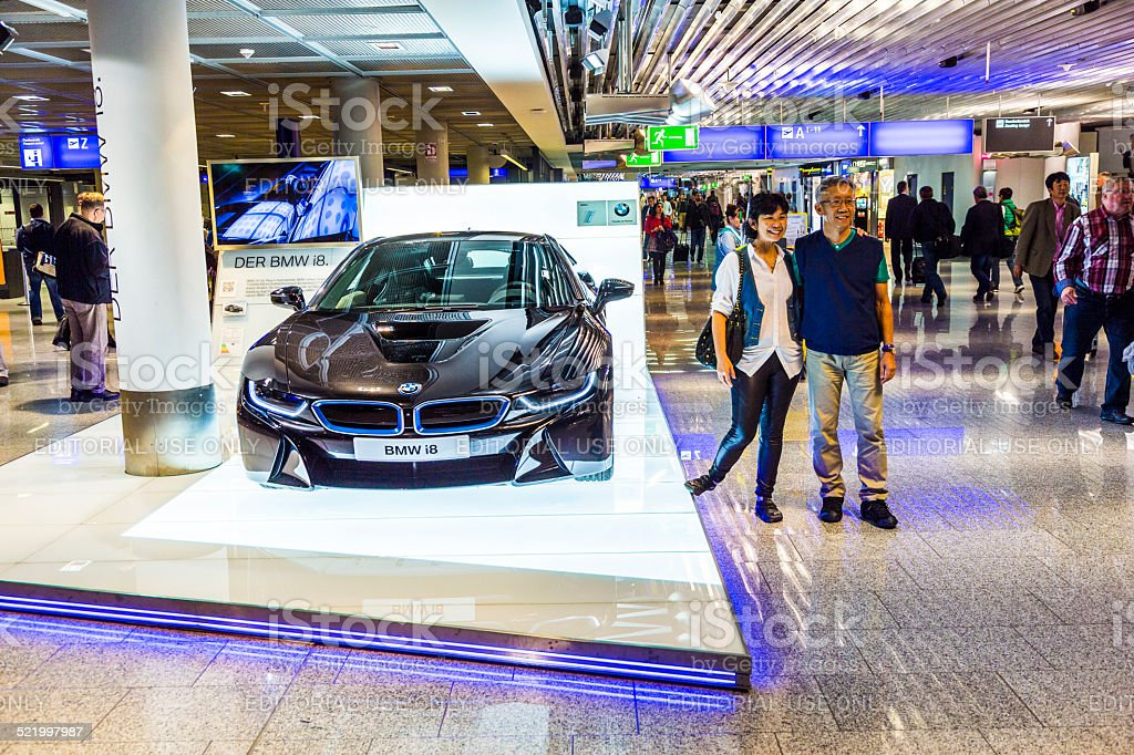 people look at black BMW series i4 innovation car. Advertising stand...