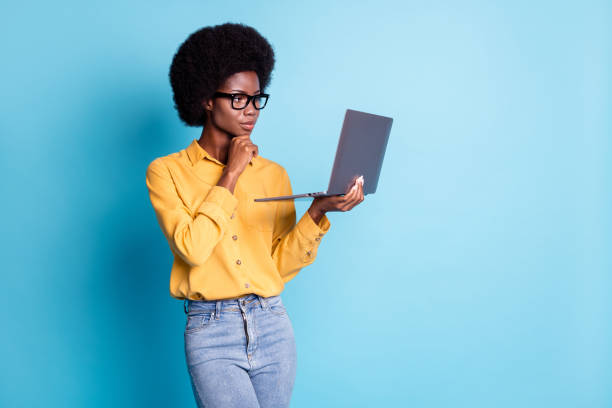 Photo of black skin big volume hairstyle serious ponderous woman hand chin hold netbook try find solution programming problem wear specs jeans yellow shirt isolated blue color background stock photo