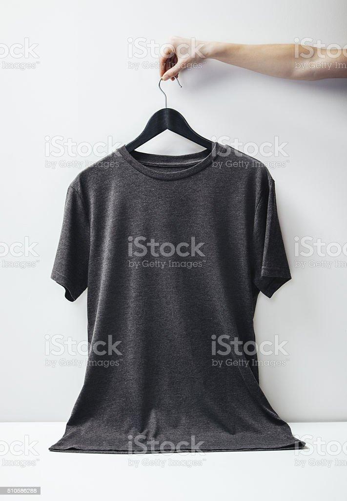 Photo of black tshirt holding on white background stock photo