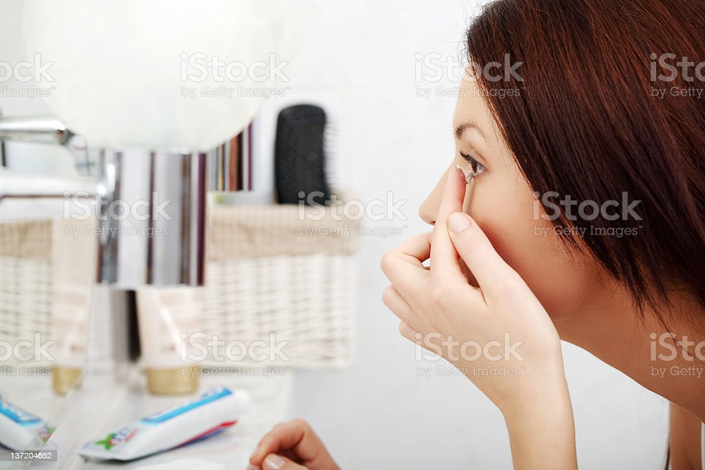 Photo of brunette woman inserting a contact lens stock photo