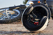 istock Photo of car, helmet and motorcycle on the road, the concept of road accidents. 1287455484