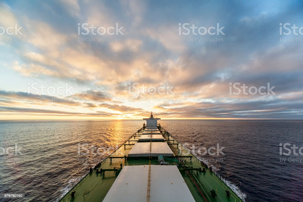 HDR photo of cargo ship at sea against sunset stock photo