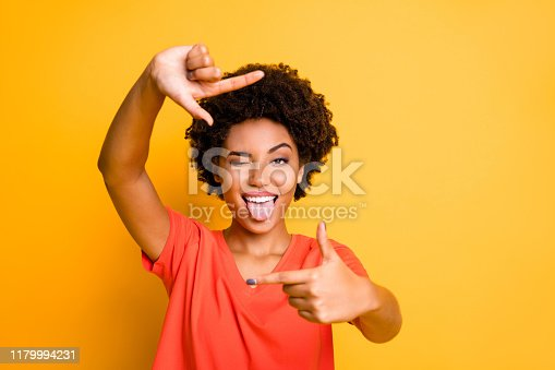 Photo of charming cut flirty black girlfriend showing you cadre frame, pretending to be photographing tongue out blinking isolated with yellow vivid color background