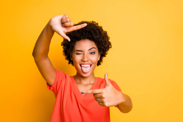Photo of charming cut flirty black girlfriend showing you cadre frame pretending to be photographing tongue out blinking isolated with yellow vivid color background Photo of charming cut flirty black girlfriend showing you cadre frame, pretending to be photographing tongue out blinking isolated with yellow vivid color background protruding stock pictures, royalty-free photos & images
