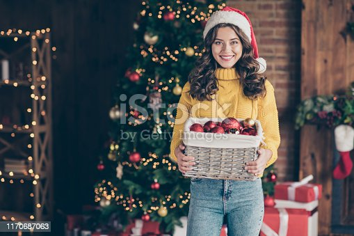 istock Photo of charming cute lady holding box with christmas toys balls while wearing red hat jeans denim yellow pullover 1170687063