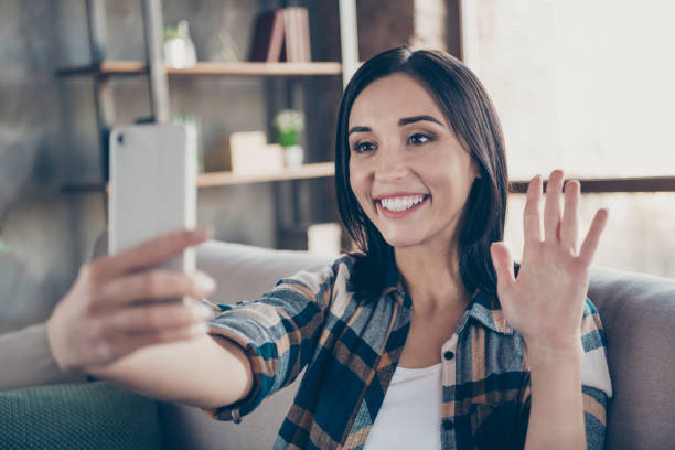photo of charming lady holding telephone making selfies speaking skype waving palm saying hi sitting comfort sofa wear casual checkered shirt apartment indoors - skype imagens e fotografias de stock