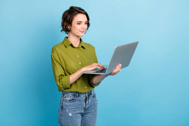 Photo of charming lady short hairstyle hold netbook hand touchpad wear jeans green shirt isolated blue color background stock photo