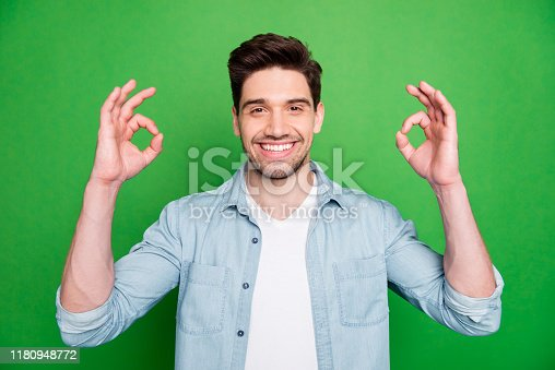 Photo of cheerful attractive handsome bearded man smiling toothily showing you, double ok sign isolated over green vivid color background