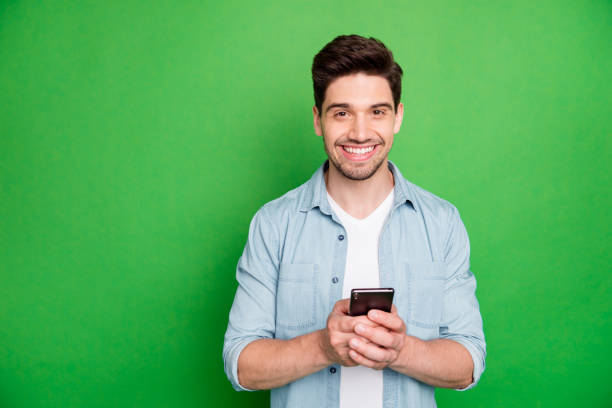 Foto von fröhlichen braun behaarten stattlichen Blogger browsing durch sein Telefon auf der Suche nach Ideen in seinen sozialen Medien isoliert über grün lebendige Farbe Hintergrund zu posten – Foto