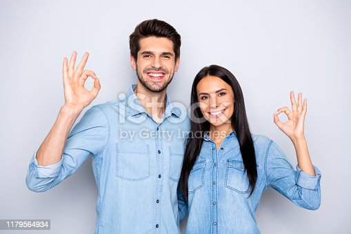 Photo of cheerful charming cute trendy stylish couple of two people standing, together wearing jackets of denim showing you ok sign isolated over grey color background
