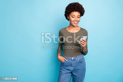 Photo of cheerful cute nice attractive black woman wearing green sweater, standing confidently with her hand in pocket smiling cheerfully isolated over vivid blue color background