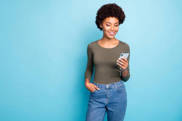 Foto von fröhlichen netten schönen schönen schwarzen Frau trägt grünen Pullover steht selbstbewusst mit der Hand in der Tasche lächelnd fröhlich isoliert über lebendige blaue Farbe Hintergrund – Foto