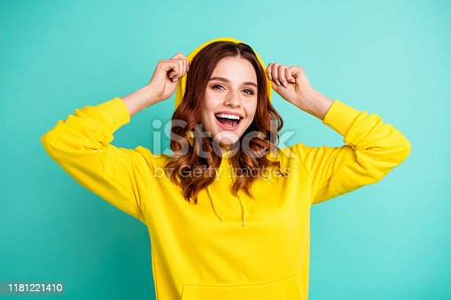 Photo of cheerful cute nice charming pretty sweet putting her hood on smiling, toothily beaming isolated over teal vivid color background