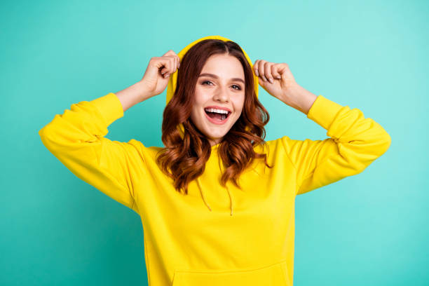 Photo of cheerful cute nice charming pretty sweet putting her hood on smiling toothily beaming isolated over teal vivid color background Photo of cheerful cute nice charming pretty sweet putting her hood on smiling, toothily beaming isolated over teal vivid color background hood clothing stock pictures, royalty-free photos & images