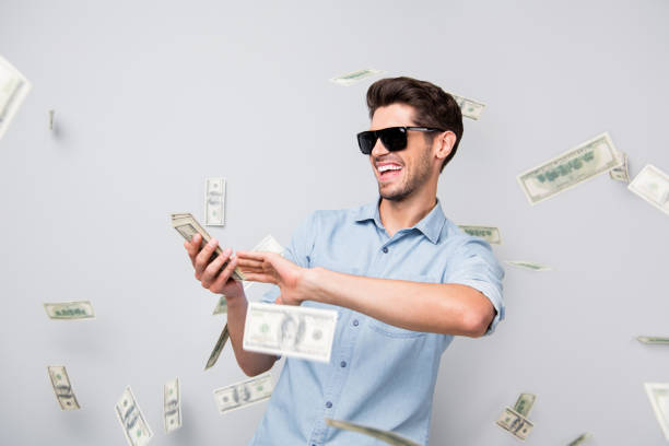 photo of cheerful excited ecstatic overjoyed man throwing money away showing his wealthiness wearing denim isolated over grey color background - throw money away stock pictures, royalty-free photos & images