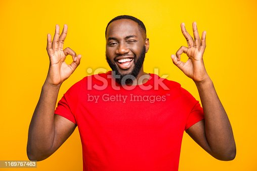 istock Photo of cheerful funny black man blinking you giving hint that everything is perfect while isolated with yellow background 1169767463