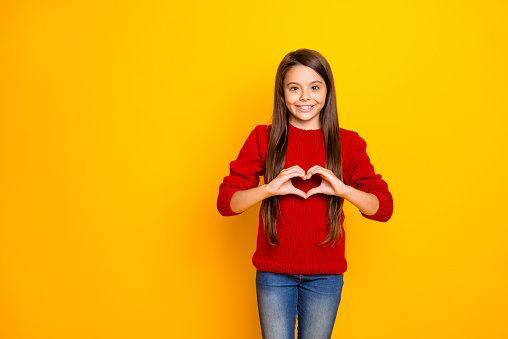 Photo of cheerful nice charming schoolgirl showing you heart shape sign being, brunette haired wearing jeans denim smiling toothily isolated over vivid color yellow background