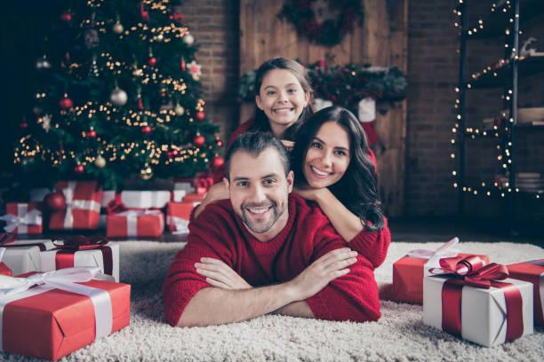 foto van vrolijke optimistische vriendelijke familie mensen mama papa schoolmeisje het dragen van rode truien toothily glimlachend binnenshuis vieren kerst samen - christmas family stockfoto's en -beelden