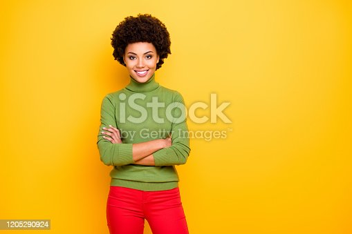Photo of cheerful positive cute nice pretty charming woman with hands, folded in red trousers smiling toothily near empty space isolated bright color yellow background
