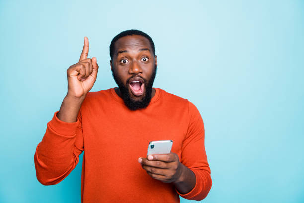 Photo of cheerful positive handsome casual man pointing up with forefinger with excitement on face holding telephone isolated vivid color blue background stock photo