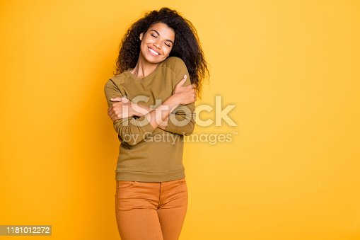 istock Photo of cheerful toothy beaming cute nice charming attractive black woman wearing orange pants trousers enjoying her newly bought sweater isolated over vivid color background 1181012272
