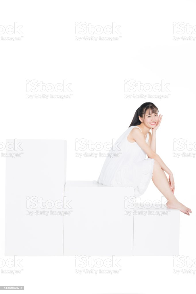 photo of cheerful woman wearing white dress sitting over white background stock photo