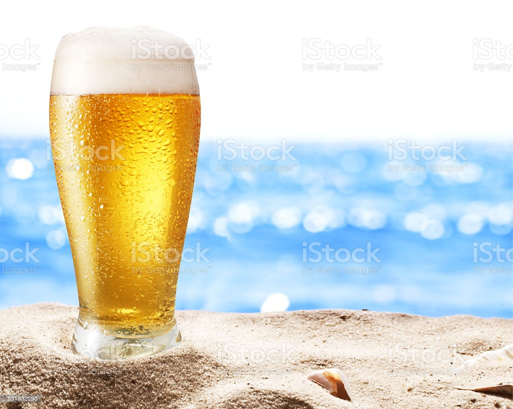 Photo of cold beer botle in the sand. stock photo