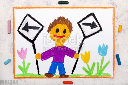 istock Photo of colorful drawing: Left and right arrow signs. Future and past concept. Smiling boy holding two signs. 1213942183