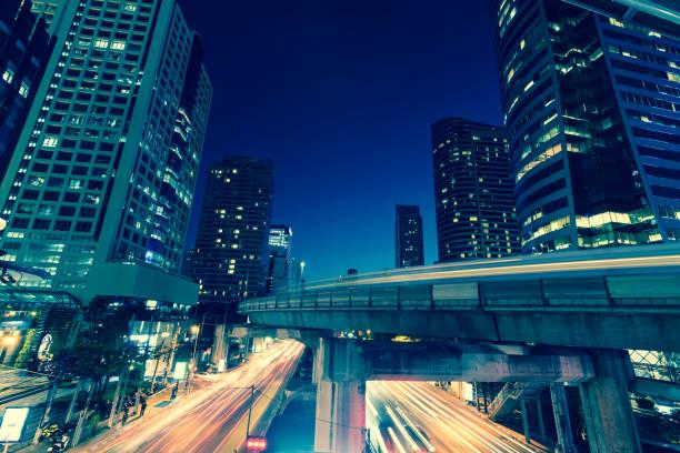 商業オフィス建物外観の写真。交通ラッシュ、バンコクでの長い exposur の光で下の高層ビルの夜景。 ストックフォト