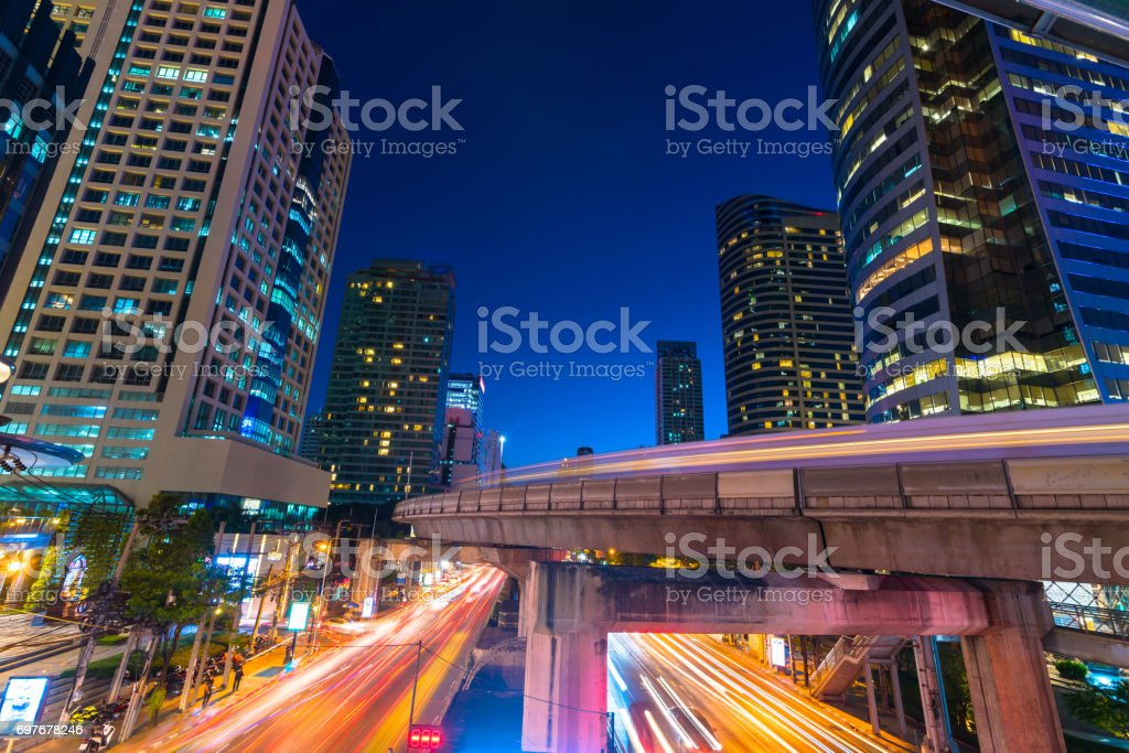 Photo Of Commercial Office Buildings Exterior. Night View At Bottom  Skyscrapers With Light Of Traffic