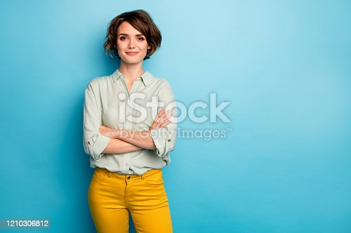 istock Photo of cool attractive business lady short hairstyle friendly smiling responsible person arms crossed wear casual green shirt yellow pants isolated blue color background 1210306812
