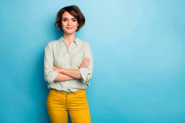 Photo of cool attractive business lady short hairstyle friendly smiling responsible person arms crossed wear casual green shirt yellow pants isolated blue color background stock photo