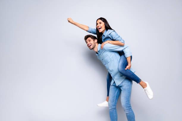 foto av cool pair guy holding lady piggyback låtsas flygning upp med super powers slitage casual jeans kläder isolerade grå färg bakgrund - superwoman barn bildbanksfoton och bilder