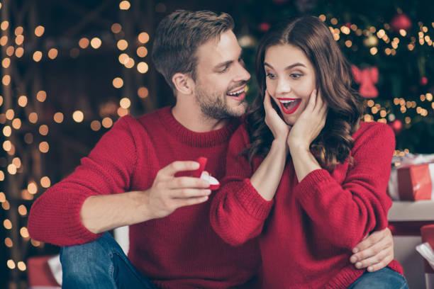 foto av par i dekorerade garland lights room guy ge lady oväntade engagera ring box väntar svar sitter mysigt nära x-mas träd inomhus slitage röda tröjor - förlovningsring bildbanksfoton och bilder