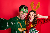 istock Photo of crazy couple making selfies sticking tongues winking eyes v-signing wear funky ugly ornaments jumpers isolated red color background 1175499210