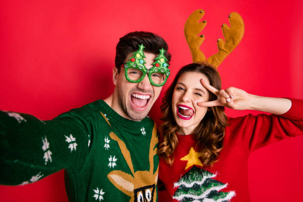 Photo of crazy couple making selfies sticking tongues winking eyes v-signing wear funky ugly ornaments jumpers isolated red color background Photo of crazy couple making selfies sticking tongues winking eyes v-signing, wear funky ugly ornaments jumpers isolated red color background ugliness stock pictures, royalty-free photos & images