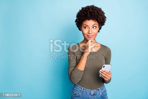 Photo of cunning smirking puzzled interested dark skinned youngster, touching her chin in thought of what to post to her profile on social media wearing jeans denim isolated over vivid color blue background