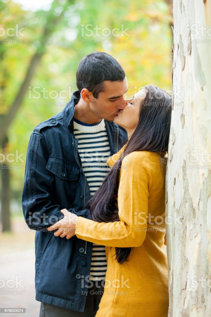 Photo Of Cute Couple Hugging And Kissing Near Tree On The Wonderful Autumn Park Background Royalty