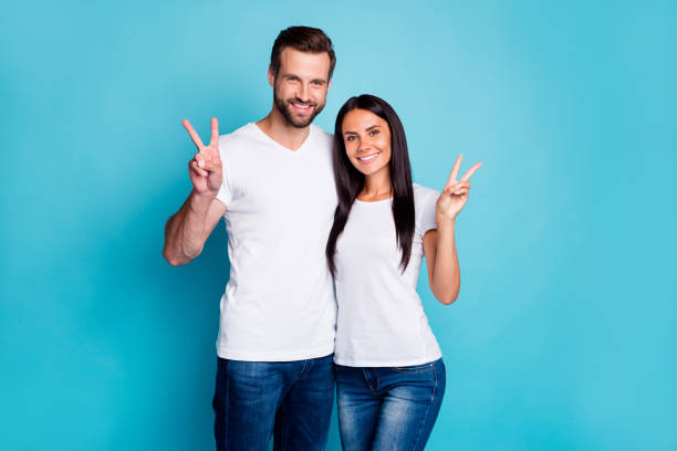 photo of cute marriage pair showing v-sign symbols wear casual outfit isolated blue background - pics for cool girl stock pictures, royalty-free photos & images