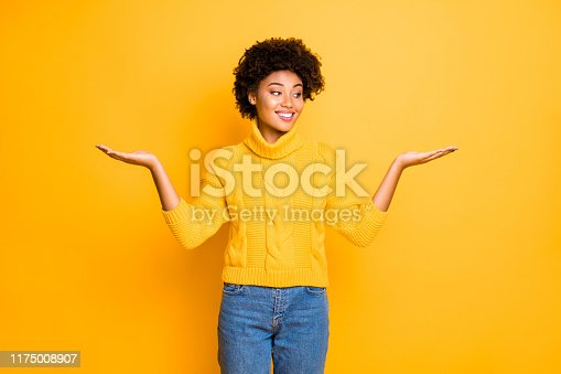 933380808 istock photo Photo of dark skin funny lady holding two new products on arms proposing best prices wear warm knitted pullover isolated yellow background 1175008907